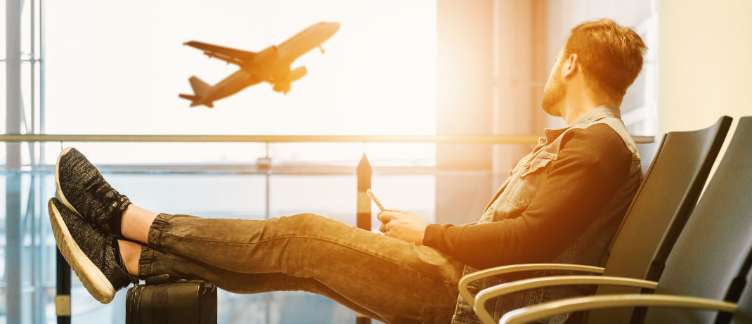 flugangst überwinden mann beobachtet entspannt startendes flugzeug